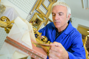 Man restoring mirror with gold leaf