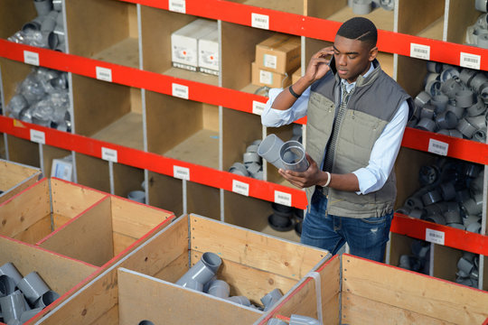 worker with clipboard calling on smartphone at warehouse