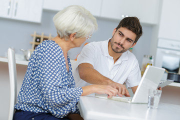 young man and his grandma working together on laptop