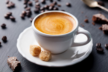 Coffee espresso in white cup on black slate background