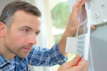 Man installing alarm keypad