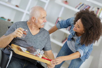 smiling nurse giving food to senior man at home