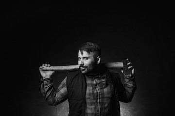 Strong smirking seductive worker holding axe. Adult woodsman on dark background, confident lumberjack portrait closeup. Sexy rural male, strength concept