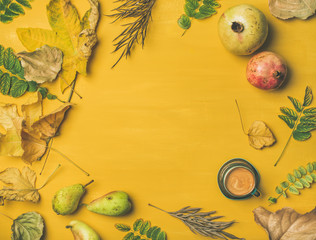 Fall background, texture, pattern. Flat-lay of Autumn harvest fruit, espresso cup and leaves over mustard yellow table, top view, copy space. Pomegranates, pears. Thanksgiving day concept