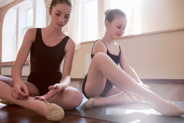 Future ballerinas. Young ladies in class. Happy girls stretching, sensibility from childhood. Gym background, healthy youth lifestyle, femininity concept