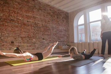 Healthy children lifestyle. Gymnastics exercises. Teenage sport with female instructor, yoga for kids. Stretching girls in studio. Gym background, health concept