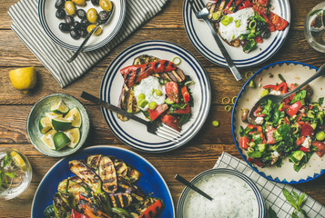 Flat-lay of healthy dinner table setting. Fresh salad, grilled vegetables with yogurt sauce, pickled olives, lemon water over wooden background, top view. Clean eating, vegan, vegetarian food concept