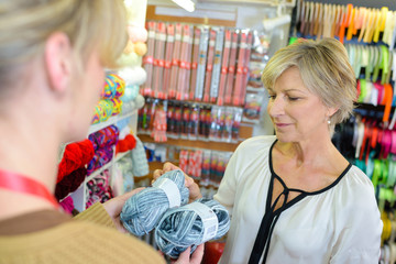 Two women in craft shop holding balls of wool
