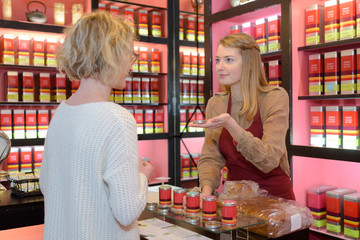 woman choosing tea in grocery store