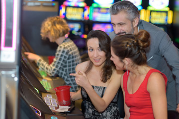 beautiful young people near slot machine in a casino