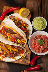 Three Mexican tacos with marbled beef, black Angus and vegetables on old rustic table. Mexican dish with sauces guacamole and salsa in bowls. top view