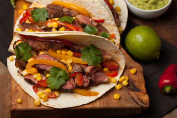 Three Mexican tacos with marbled beef, black Angus and vegetables on old rustic table. Mexican dish with sauces guacamole and salsa in bowls