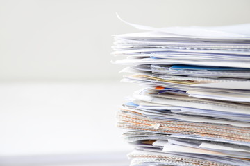 Pile of financial documents on white table with copy space for text.