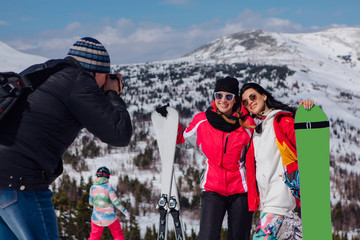 Photographer takes picture of two young women with ski and snowboard