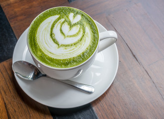 Hot green tea with milk in white cup