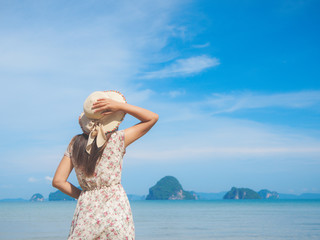 Woman in summer vacation wearing straw hat and beach dress enjoying the view at the ocean. Travel and summer concept.