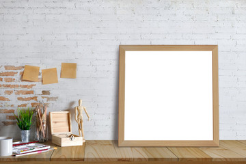 Mock up poster or photo frame and artist supplies on table hipster minimalism loft desk space, copy space