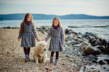Two little twin sisters on a walk with dog on the beach.