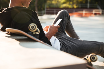 Cropped image of a smiling skateboarder looking at mobile phone