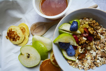 hearty Breakfast, fruit muesli for Breakfast with honey and pancakes on the table