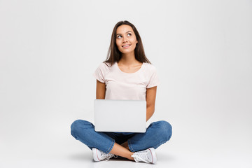 Photo of young thinking brunette woman, holding and using laptop, while sitting with crossed legs