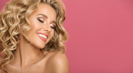 Wall Mural - Blonde woman with curly beautiful hair smiling on pink background.