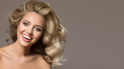 Wall Mural - Blonde woman with curly beautiful hair smiling on gray background.