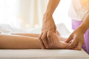 Close-up of woman doing foot massage at spa.