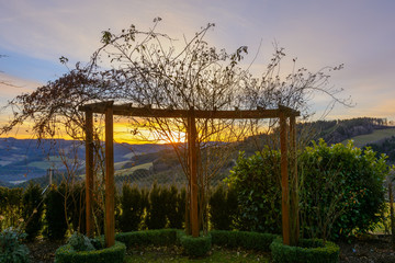 Glorious epic sunrise on a winter morning with a colorful sky looking through a rose pergola towards the horizon over hills and valleys