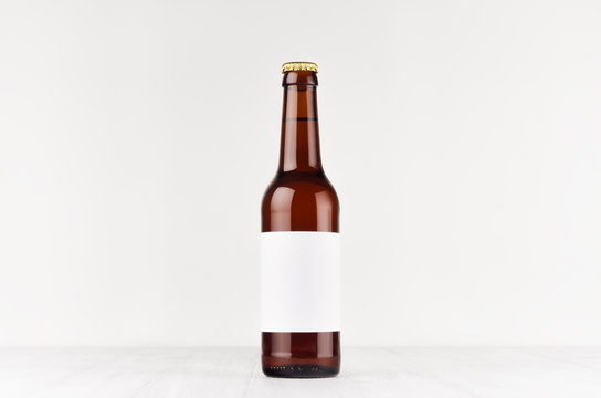 Brown longneck beer bottle 330ml with blank white label on white wooden board, mock up. Template for advertising, design, branding identity.