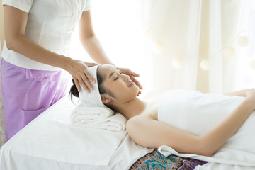 Young beautiful woman having face massage relaxing in spa.