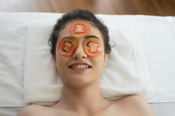 Young woman with fresh tomatoes mask in spa.