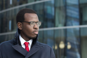 Outdoor portrait of handsome African businessman pictured in urban environment dressed in coat with lifted collar looking to street through eyeglasses with expression of serious concentration on work