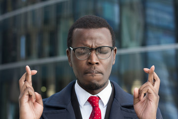 Horizontal headshot of young African businessman pictured in urban environment feeling worried and uneasy with eyes closed, lips pressed and fingers crossed willing to avoid unpleasant consequences