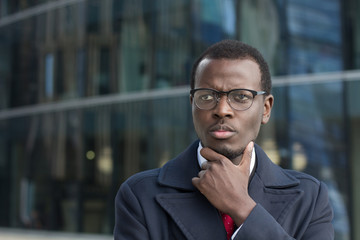 Outdoor closeup of young dark-skinned executive in spectacles standing in street, touching chin with palm in gesture of thinking and weighing decision crucial for his business
