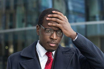 Outdoor closeup of handsome African businessman dressed in smart coat, wearing glasses covering head with hand with puzzled and troubled look as if experiencing problem or challenge to solve at work