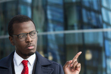 Horizontal portrait of young dark-skinned male in spectacles standing in street surrounded with skyscrapers looking rightwards, pointing with finger or making protesting gesture to prevent action