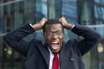 Outdoor image of emotional African male wearing formal clothes and eyeglasses staring at camera with round eyes, extremely excited, pressing fits to head in sign of surprise and euphoria, screaming