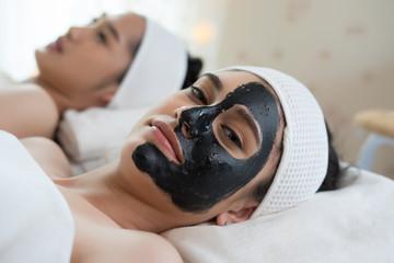 Beautiful woman getting facial mask at beauty salon.