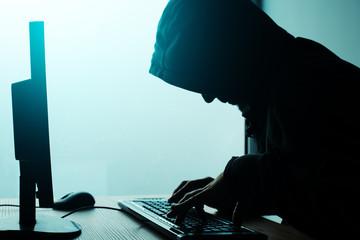 Hooded computer hacker hacking network