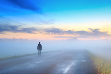Silhouette of a man walking on the road in the fog at sunset