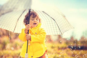 Having fun under the rain, toddler girl with umbrella.