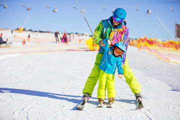 Father or instructor teaching little skier how to make turns