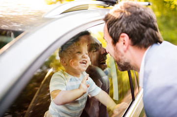 Little boy in the car looking at his father.