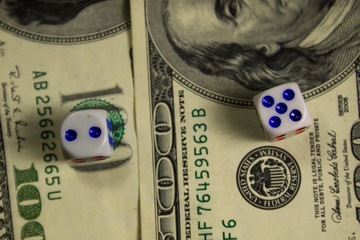 White dices on a hundred dollar bills closeup