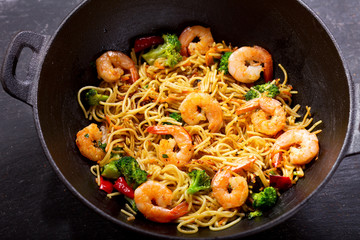 Stir fried noodles with shrimps and vegetables in a wok