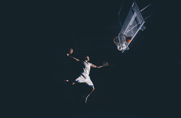 Man jumping with basketball in court