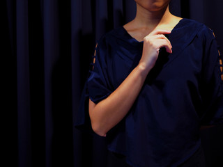 Woman wearing blue black shirt with shoulder hole details, with black curtain background, left hand holding another elbow, and right hand putting up like to do the critical thinking