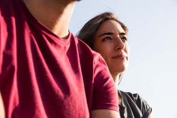 Young confident woman sitting near boyfriend under blue sky and looking away dreamily.