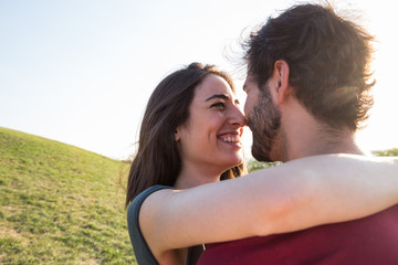 Young happy woman embracing with man in sunlight on background of green summer lawn.